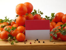 Monaco flag on a wooden panel with tomatoes isolated on a white Royalty Free Stock Photography
