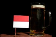 Monaco flaga z piwnym kubkiem na czerni Zdjęcie Stock