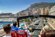 Monaco, France – July 24, 2017: Group of touristic people traveling by tour bus in luxury Monaco (Monte carlo). Sunny day, blue sky, mountain, building stock photo
