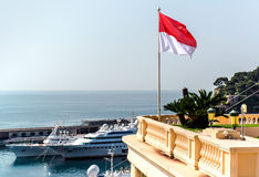 Monaco. National flag of of the Principality of Monaco and view of port stock images