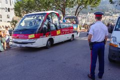 Monaco, Tourist bus. The tourist bus with audio guides in different languages departments from the Prince`s Palace. A policeman watches the order stock photography