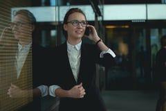 Monan op slimme telefoon - jonge bedrijfsvrouw in bureau Stock Afbeeldingen