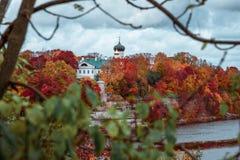 Monastère chrétien antique en parc coloré d'automne sur les banques de la rivière sur un fond du ciel nuageux photographie stock