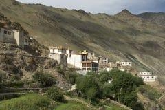 Monasterio budista de Mounaeus Gonpa, rezo blanco antes del soporte en la cuesta de una colina verde entre los árboles, Zanskar,  Imagenes de archivo