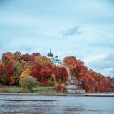 Monasterio cristiano antiguo en parque colorido del otoño en los bancos del río en un fondo del cielo nublado fotografía de archivo libre de regalías