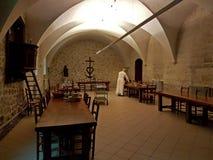 Monastero di St Michael in Frigolet, Francia - possono 28, 2017: Un monaco in un abito talare bianco mette la tavola nel refettor fotografie stock