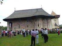 Monastero di umore in Bucovina fuori durante la massa del 15 agosto con qualche gente in vestiti tradizionali in Romania Immagine Stock