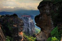 Monastero nelle montagne nella distanza, Meteora, Grecia Fotografia Stock