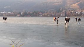 Monasterolo del Castello, Bergamo, Italy. People skating and walking on the frozen lake. Winter season stock footage