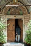 Monastery in Cyprus. Cyprus - April 17, 2006: A man enters the church of the Panagia Chryssorogiatissa Monastery, a listed UNESCO World Heritage Site on the stock photography