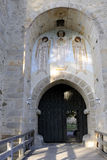 Monastery entrance. Historical monastery entrance, shadows on bridge, angles painted on stone walls Stock Photo