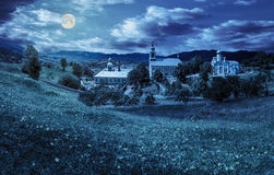 Monastery on the hillside at night. Composite image of green Monastery in mountains on hillside with grass and dandelions at night in full moon light Stock Photo