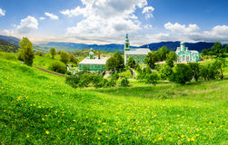 Monastery on the hillside at sunrise. Composite image of green Monastery in mountains on hillside with grass and dandelions in morning light Stock Images