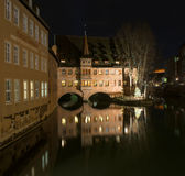 Monastery Holy Spirit Hospice. On the river bank and bridge at night in Nuremberg, Germany Royalty Free Stock Images