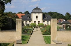 Monastery in Nordrhein Westfalen. View of a monastery with monastery wall, the main building, the entrance to the monastery gardens, monastery garden under blue Royalty Free Stock Photos
