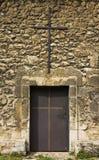 Monastery old metal  door. With a cross, stone wall, metal cross on top of the door Royalty Free Stock Image