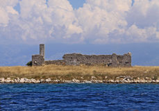 Monastery ruins on an island, croatia. Ruins of an ancient monastery on a small islad south-east of losinj island, Croatia with mountains of the mainland and stock photography