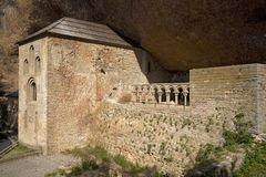 The Monastery of San Juan de la Pena, Jaca, in Jaca, Huesca, Spain, carved from stone under a great cliff.  It was originally buil Stock Photography