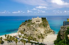 Monastery Sanctuary church of Santa Maria dell Isola on top of rock Tyrrhenian Sea and green palm trees, blue sky white clouds in stock photo