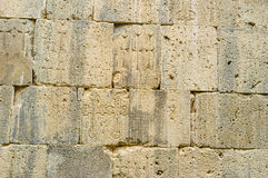 The Monastery wall. The old wall of St Peter and Paul Cathedral with preserved medieval carvings of the cross-stones (khachkars), Tatev Monastery, Syunik Royalty Free Stock Photo
