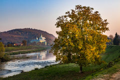 Monasteryon a hill  and tree near river in hazy autumn sunrise. Monastery on a hill near river at the foot of the mountain. tree with yellow foliage on near Stock Images