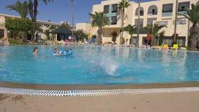 Monastir,突尼斯- 2018年6月05日:在深游泳池的滑稽的女孩少年潜水在旅馆里 跳跃在水中的愉快的女孩 股票视频