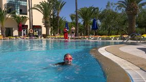 Monastir,突尼斯- 2018年6月05日:落在水游泳池的游泳的玻璃的女孩少年在度假旅馆里 影视素材