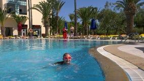 Monastir, Тунис - 5-ое июня 2018: Подросток девушки в плавая стеклах падая в бассейн воды в курортном отеле видеоматериал
