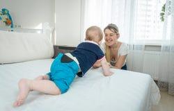 10 Monate alte Baby, die auf Bett in Richtung zu lächelnder junger Mutter kriechen Lizenzfreie Stockfotos