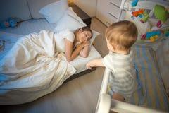 9 Monate alte Baby, die im Feldbett stehen und seins aufwachen, ttired schlafende Mutter stockfoto