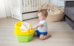 10 Monate alte Baby, die mit Babykammertopf spielen stockfotos