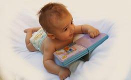 3 Monate alte Baby, die mit Buch spielen Lizenzfreie Stockbilder