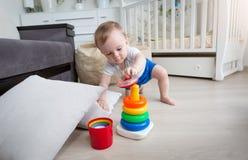 9 Monate alte Junge, die auf Boden am Wohnzimmer kriechen und f erreichen Stockbild