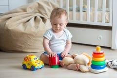 10 Monate alte Kleinkindjunge, die auf Boden sitzen und mit Spielwaren spielen Stockbild