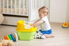 10 Monate alte Kleinkindjunge, die auf Boden sitzen und Plastiktoilettentopf spielen Stockfotos