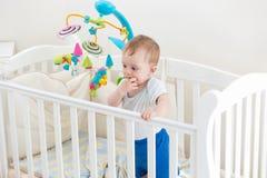 10 Monate alte Kleinkindjunge, die im weißen hölzernen Feldbett stehen Stockfotografie
