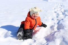 18 Monate Baby, die auf Schnee sitzen Lizenzfreie Stockfotos