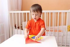 20 Monate Baby, die Haus aus Papierdetails konstruieren Lizenzfreies Stockfoto