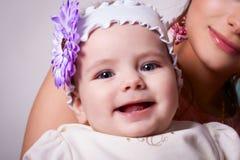 6 Monate Baby, die mit einer Blume auf ihrem Kopf lächeln Stockbild