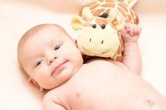 2 Monate Baby mit dem weichen Spielzeuglächeln Stockfotografie