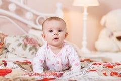 6-monatiges Baby, das auf Bett legt Lizenzfreie Stockbilder
