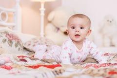 6-monatiges Baby, das auf Bett legt Lizenzfreie Stockfotos