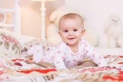 6-monatiges Baby, das auf Bett legt Stockfoto