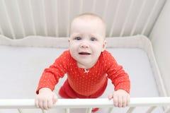 6-monatiges Baby, das im weißen Bett schreit Stockbilder