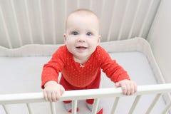 6-monatiges Baby steht im weißen Bett und lächelt Lizenzfreie Stockbilder