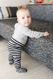 6-monatiges Baby steht Sofa bereit Stockfotografie