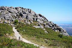 Monchique mountain landscape, Portugal. Mountain path leading to large rocks with across the Monchique mountains and countryside, Foia, Algarve, Portugal Royalty Free Stock Photo