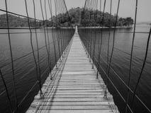 Monchrome-Seilbrücke verweisen zur einsamen Insel über dem See Stockfotos