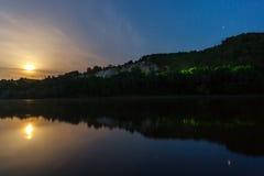 Mond im sternenklaren nächtlichen Himmel reflektiert im Fluss Lizenzfreies Stockbild