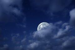 Mond und Sterne im bewölkten Himmel Stockfotos